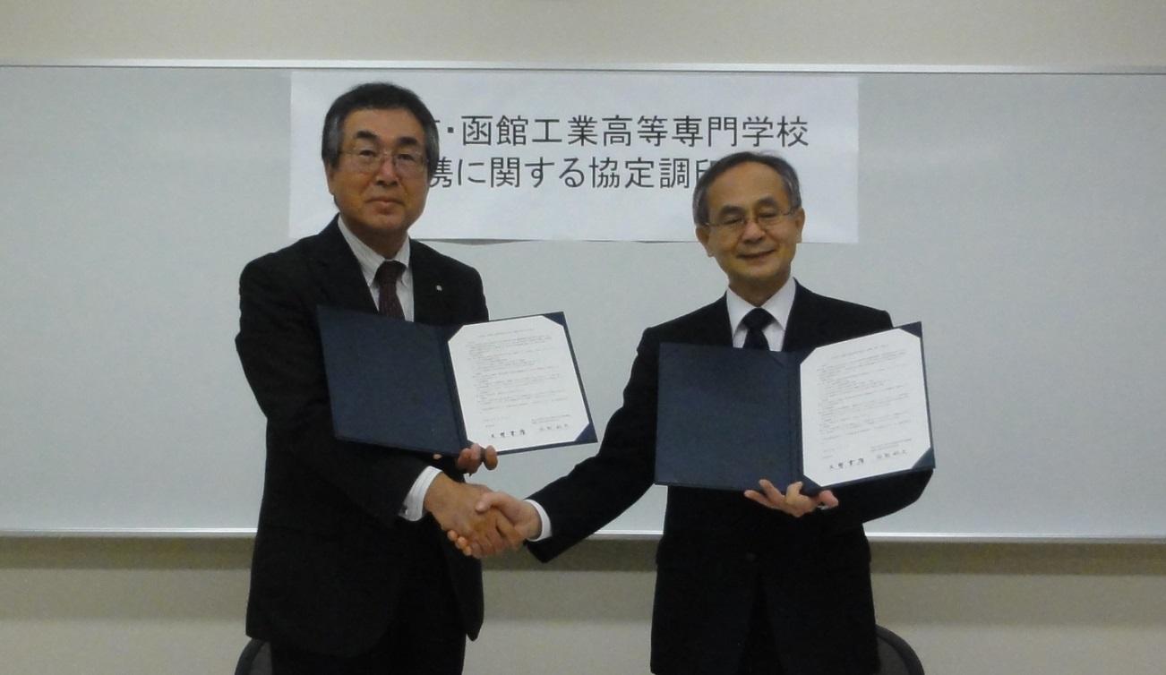 協定書に調印し握手する岩熊校長(右)と大野町長